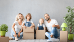happy family smiling in moving boxes-best charlotte home loans blog